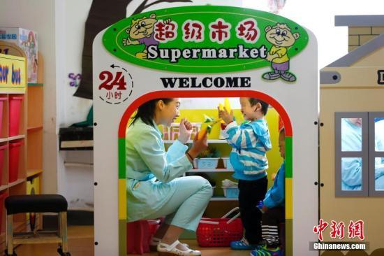 资料图:孤残儿童在老师的带领下学习购物。中新社记者 富田 摄