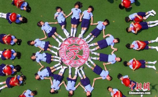 资料图:江苏扬州一幼儿园组织即将毕业的孩子们在操场上摆出创意新颖的图案拍摄个性毕业照,留下独特的美好回忆。孟德龙 摄