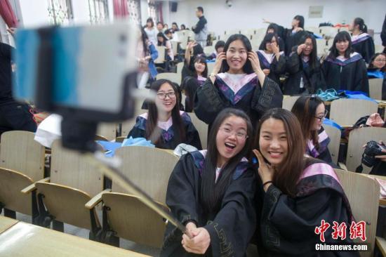 5月23日,山西太原,山西大学毕业生在校园拍摄毕业大合影。随着一年一度的毕业季到来,中国各地高校的毕业生们也即将离开校园,学子们纷纷用别样的毕业照与大学校园告别。中新社记者 张云 摄
