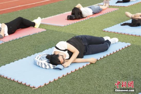"""5月25日下午,武汉华夏理工学院操场上,80余名""""睡觉""""的女生引人注目。据悉,这是该校心语心理健康协会主办的一场行为秀。主办方表示,不少大学生长期熬夜,开展此行为艺术秀活动,希望呼吁学生关注睡眠质量,养成良好作息习惯。刘涌志 摄"""