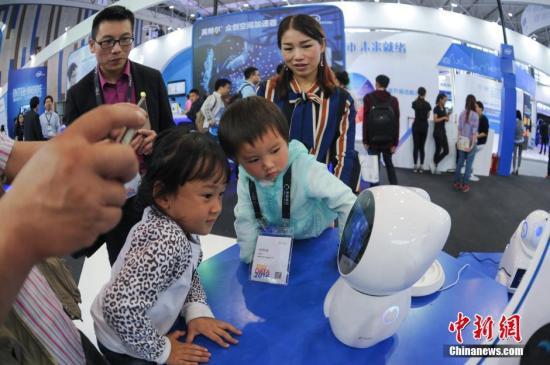 5月25日,两名儿童在英特尔(Intel)展台观赏育儿机器人。当日,2016中国大数据产业峰会暨中国电子商务创新发展峰会(数博会)在贵阳开幕。本届数博会为期5天,将组织举办大数据博览会和多个行业领域分论坛。2016数博会展览会将分别从大数据分析与应用、数据中心和配套产品、智能制造及设备、互联网创新应用、电子商务五大板块,集中展现全球高端技术和数据的最新应用。参展企业和机构300余家,包括高通、戴尔、富士康、华为、腾讯、百度、阿里巴巴、京东、乐视等全球大数据领域企业。<a target='_blank' href='http://www.chinanews.com/'>中新社</a>记者 贺俊怡 摄