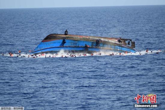 资料图:利比亚近海海域,一艘满载难民的船只即将倾覆,船上的难民纷纷跳海逃生。
