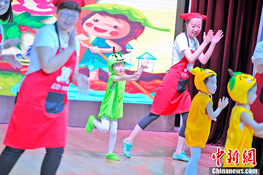 资料图:幼儿园的小朋友和家长一起表演节目。中新社记者 佟郁 摄