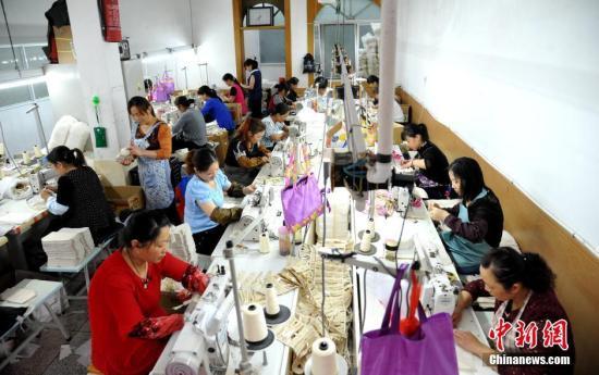 资料图:学校附近的制衣厂内,陪读妈妈利用空余时间做工挣取生活费。中新社记者 韩苏原 摄