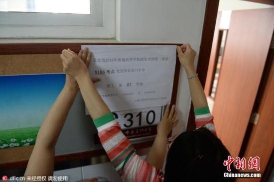2016年6月3日,北京,东直门中学考点,教室外已贴上了统一印制的考场信息,上面显示着考点编号、名称及具体的考场号。教室内设置了约30个考生座位,座位与座位之间的距离约为80厘米以上。两位考务老师手持一叠写有学生姓名、准考证号的桌签走进教室,按考场座位安排表逐一贴在桌子上。随后,一位老师在黑板上写下了当科开考的科目、考试时间和试卷份数。图片来源:东方IC 版权作品 请勿转载