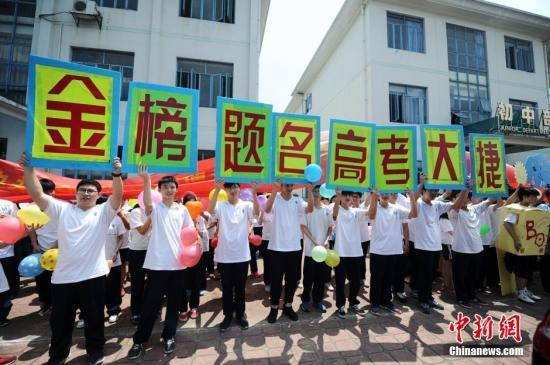 资料图:2016年6月6日下午,湖南长沙同升湖实验学校的2000多名师生及部分家长高举横幅标语为高考学子呐喊加油。 杨华峰 摄