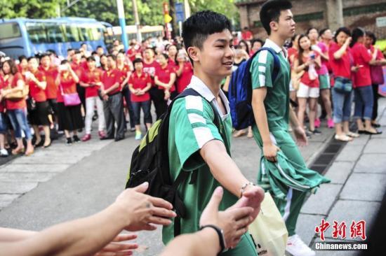 6月7日,一名考生身后站满了身穿红衣为考生助威的家长。当日,2016年高考拉开序幕,广东高考考生报考总人数73.3万人,报考总人数比2015年减少2.1万人。其中,符合报考条件的省外户籍随迁子女考生有9500多人。中新社记者 陈骥F 摄