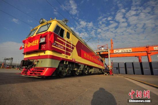 """6月8日,中国铁路正式启用中欧班列统一品牌,统一品牌中欧班列当日分别从成都、重庆、郑州、武汉、长沙、苏州、东莞、义乌等八地始发。今后,中国开往欧洲的所有中欧班列将全部采用这一品牌。中欧班列品牌标识以奔驰的列车和飘扬的丝绸为造型,融合中国铁路路徽、中国铁路英文缩写、快运班列英文字母等元素,以中国红、力量黑为主色调,凸显出中国铁路稳重、诚信、包容、负责和实力的品牌形象。中欧班列是指按照固定车次、线路、班期和全程运行时刻开行,往来于中国与欧洲以及""""一带一路""""沿线各国的集装箱国际铁路联运班列。截至目前,中国已累计开行中欧班列1700列以上。图为统一品牌中欧班列。 吴正琪 摄"""