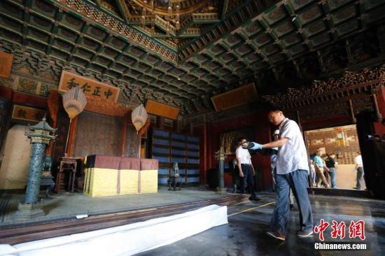 """6月11日,中国第11个文化遗产日,故宫博物院围绕文化遗产日主题""""让文化遗产融入现代生活""""开展了一系列活动。图为工作人员进行养心殿区域文物撤陈工作。""""养心殿研究性保护项目""""作为""""故宫古建筑整体修缮保护""""工程的重要项目已于2015年12月18日启动,自项目启动以来,目前已完成古建原状影像采集工作,为故宫的古建修缮项目建立完整的视听档案材料;目前正在进行养心殿文物建筑相关的保护修复工作的研究与实施;同期开展可移动文物的记录、研究和修复。养心殿可移动文物的撤陈工作已于5月30日启动,预计在3个月内完成。<a target='_blank' href='http://www.chinanews.com/'>中新社</a>记者 盛佳鹏 摄"""