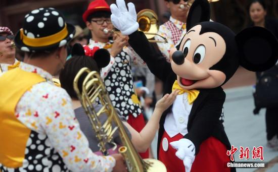 """资料图:迪士尼乐园举行""""米奇童话专列""""主题巡游。上海迪士尼开幕在即,从14日开始为期3天的上海迪士尼乐园开幕庆典系列活动吸引了近千名嘉宾前来感受迪士尼的无穷魅力。 汤彦俊 摄"""