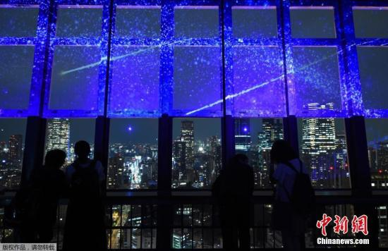 资料图:游客们在日本东京塔上欣赏夜景。