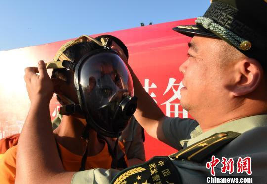 图为市民体验消防空气呼吸器。 周毅 摄