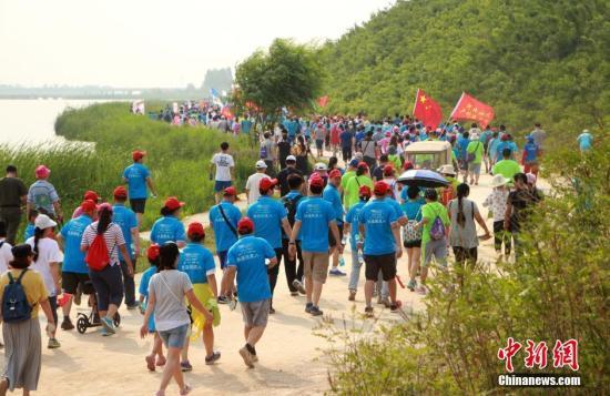 """6月18日,由石家庄市体育局""""全城热练""""全民健身品牌重点打造的精品赛事""""2016石家庄(正定)国际徒步大会"""",在河北正定滹沱河风景区举行。随着""""徒步走""""成为世界性的时尚健康运动,越来越多的民众参与其中。本届徒步大会吸引了万余名爱好者参与,线路贯穿石家庄市滹沱河绿色生态长廊,主会场和起点在冀之光广场,共设立了三条徒步线路:休闲组(10公里)、健身组(20公里)、明星组(30公里),是继石家庄(正定)马拉松之后推出的又一张城市名片。图为大会进行途中。 韩冰 摄"""