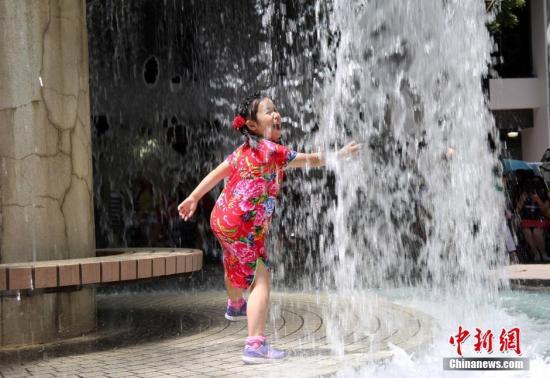 资料图:小朋友在香港公园戏水消暑。 中新社记者 洪少葵 摄