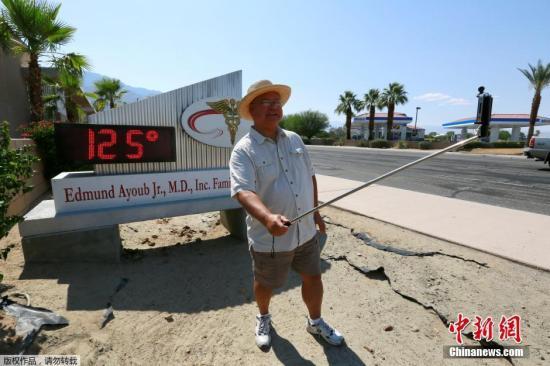 """一位棕榈泉住民在显现高温的数字温度牌前举起自拍杆。政府称热浪""""稀有而风险"""",会无形成中暑等危险,呐喊大众防止永劫刻勾留室外。"""