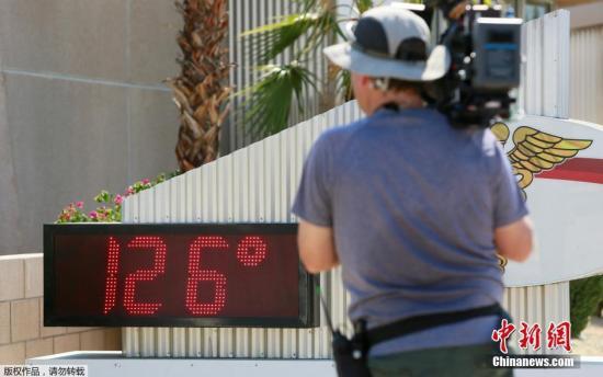 """当地时间6月20日,美国加州棕榈泉地区,电视台摄像人员对着显示数字温度计拍摄,数字面板显示当地气温已高达126华氏度,约合52摄氏度。美国西南部近日受高压脊影响,形成""""怪兽级""""热浪,南加州等多地出现异常高温。"""