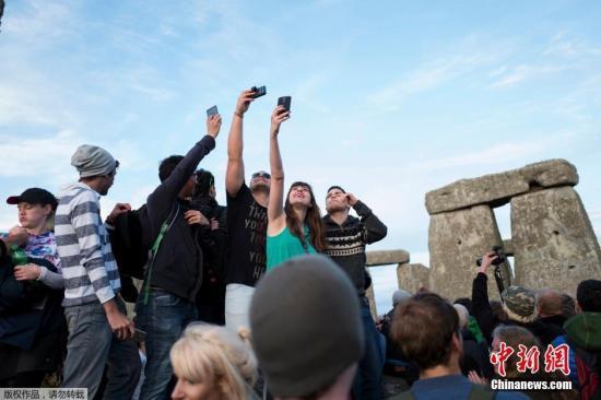 人们在巨石前高举手机自拍。