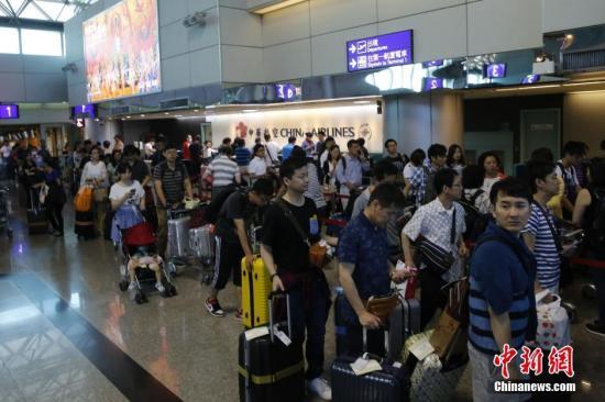 资料图:台湾桃园机场内,中华航空公司服务台前咨询航班信息或改签航班的旅客排起百余米的长队。 中新社记者 陈小愿 摄