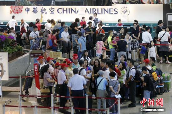 资料图:台湾桃园机场内,中华航空公司服务台前的旅客排起长队。中新社记者 陈小愿 摄