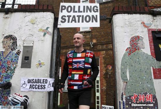 """在英国有稳定的工作和收入来源的白领们,是英国""""留欧""""阵营的有力支持者。图为一名参与投票的市民,身穿印有欧盟各国旗帜的衣服来到投票点。"""