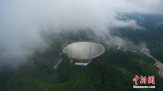 """7月3日,位于中国贵州省内的500米口径球面射电望远镜(FAST),顺利安装最后一块反射面单元,标志着FAST主体工程完工,进入测试调试阶段。FAST主动反射面由4450块反射面板单元组成,面积约25万平米,近30个标准足球场大小,用于反射无线电波。据介绍,FAST旨在实现大天区面积、高精度的天文观测,其科学目标包括巡视宇宙中的中性氢、观测脉冲星、探测星际分子、搜索可能的星际通讯信号等,其应用目标是在日地环境研究、搜寻地外文明、国防建设和国家安全等国家重大需求方面发挥作用。图为7月2日航拍安装完成前夕雾中的""""天眼""""。 中新社记者 贺俊怡 摄"""