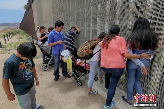 当地时间2016年7月2日,美国加州圣易西铎(San Ysidro),美墨边境两边的亲人隔着栅栏相聚,据悉,美国边境管理局允许生活在美国境内的民众与他们生活在墨西哥境内的家人周末在边境处相聚,但是需要在边境管理人员的监督下进行。