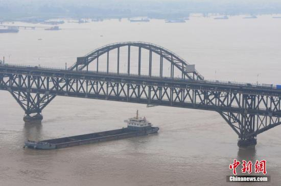 图为7月5日,船只驶过超警戒线水位的长江江西九江段。 胡国林 摄