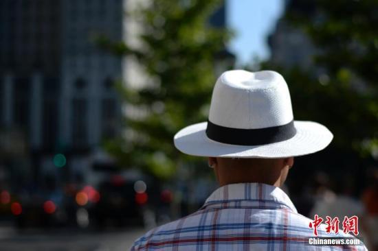 资料图:美国民众戴着遮阳帽出行躲避夏日曝晒。 中新社记者 廖攀 摄
