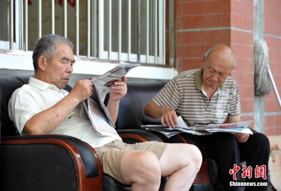 资料图:武汉洪山区通惠社区养老院安置点,2位老人悠闲地看着报纸。 中新社记者 张畅 摄