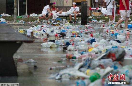 当地时间7月10日,西班牙潘普洛纳在一天的奔牛狂欢结束后,街道地上堆满了塑料瓶、啤酒罐等各种垃圾。图为狂欢者在卡斯蒂略广场上休息。