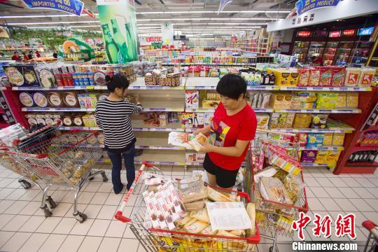 资料图:山西太原某超市员工在调配进口食品货架。张云 摄