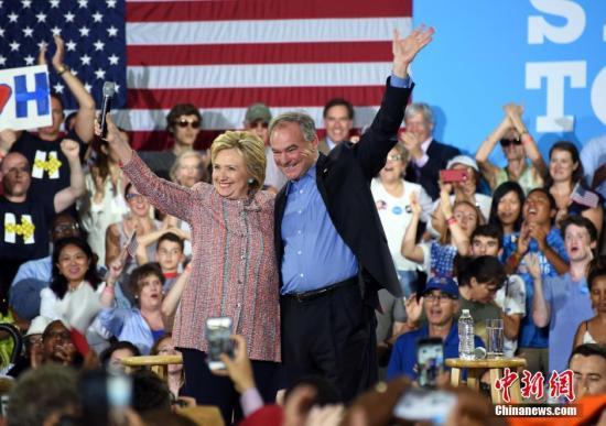 """当地时间7月14日,美国总统大选民主党""""假定提名人""""希拉里・克林顿在弗吉尼亚州费尔法克斯县举行竞选活动,弗吉尼亚州联邦参议员蒂姆・凯恩同台助选。图为希拉里(左)与蒂姆・凯恩(右)。 记者 张蔚然 摄"""
