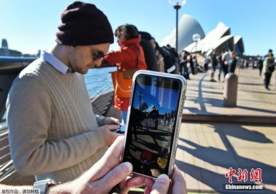 资料图:澳大利亚悉尼,数十名民众在悉尼歌剧院前玩手机游戏。