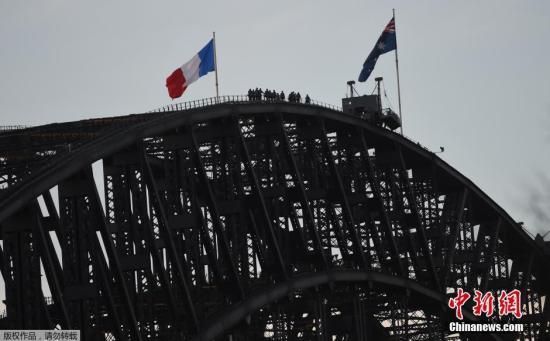 当地时间7月14日晚,法国东南沿海城市尼斯发生卡车冲撞人群事件。观看国庆节烟火表演的民众遭人驾车高速碾压,现场传出枪声,造成数十人遇难,上百人受伤。总统奥朗德紧急召开记者会宣布事件为恐怖袭击。图为当地时间7月15日,澳大利亚悉尼,悉尼海港大桥上升起法国国旗,悼念尼斯卡车袭击案遇难者。