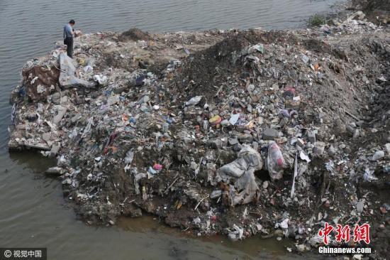 2018-12-09,江苏省海门市的江心沙农场新江海河一座桥附近偷倒的垃圾。据运载垃圾货船上的船员透露,这些垃圾也是从上海运来。图片来源:视觉中国