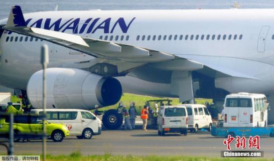 当地时间7月18日,夏威夷航空公司飞机紧急迫降在日本东京羽田机场,工作人员更换轮胎。