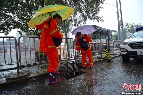 北京市气象台7月20日8时40分升级发布暴雨黄色预警信号,预计本市大部分地区仍有暴雨、局地大暴雨。山区及浅山区可能出现强降水诱发的中小河流洪水、山洪、地质灾害等次生灾害,城市部分低洼地区可能出现积水,请防范。图为市政人员正在检查排水管网。记者 金硕 摄