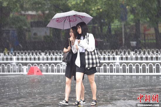 北京市气候台7月20日8时40分晋级公布暴雨黄色预警信号。图为北京市民冒雨出行。中新网记者 金硕 摄