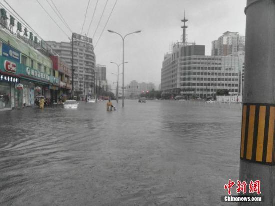 """7月20日8时40分,北京市气候台公布""""暴雨黄色预警"""",估计当日北京市大有些地区仍有暴雨、局地大暴雨。图为北京脚门地域积水重大。中新网记者 王�t 摄"""
