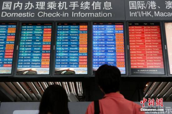 """7月19日,乘客查看显示航班信息的电子屏。当日,北京""""豪雨""""来袭,市气象台发布今年首个暴雨蓝色预警。首都机场目前有接近100个航班处在延误或者取消的状态。截至16:00,首都机场计划执行1033架次,已执行913架次。 <a target='_blank' href='http://www.chinanews.com/'>中新社</a>记者 李慧思 摄"""