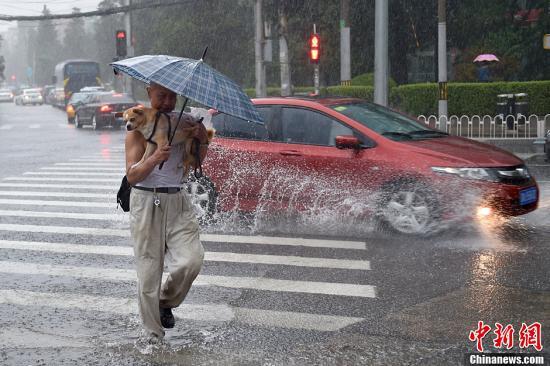 北京市气象台7月20日8时40分升级发布暴雨黄色预警信号,预计本市大部分地区仍有暴雨、局地大暴雨。山区及浅山区可能出现强降水诱发的中小河流洪水、山洪、地质灾害等次生灾害,城市部分低洼地区可能出现积水。图为北京东三环燕莎桥附近民众冒雨出行。<a target='_blank' href='http://www.chinanews.com/' >中新网</a>记者 金硕 摄