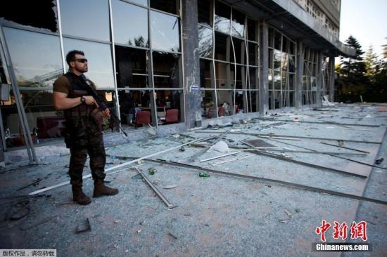 当地时间2016年7月19日,土耳其安卡拉,在政变中被毁的议会大楼和警察局大楼成为废墟,墙上有明显的子弹痕迹。土耳其特警持枪看守这些政府办公处。