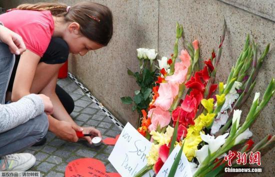 当地时间7月23日,德国民众在慕尼黑奥林匹亚购物中心附近摆放鲜花,悼念枪击案遇难者。