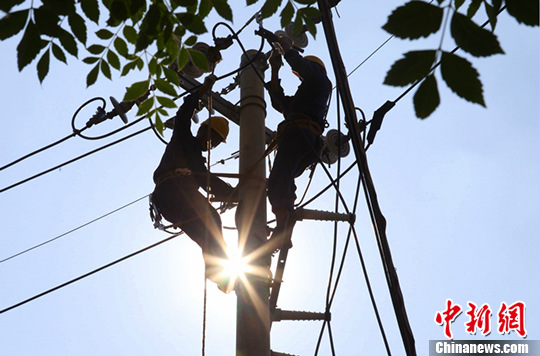 资料图:电力工人烈日下抢修。 奚青兰 摄
