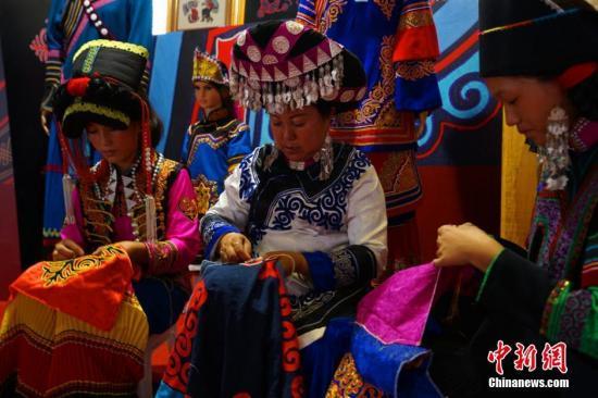 资料图:非物质文化传承人正在对彝族服装进行刺绣。邹立杨 摄
