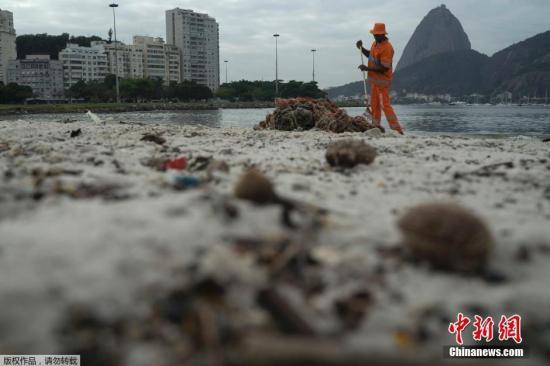 本地工夫7月30日,一位干净工人正正在巴西里约糖里包山战瓜巴推湾四周全是渣滓的专塔弗戈沙岸上清算。