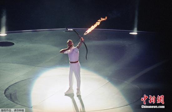 """资料图:巴塞罗那开幕式上的点火者从轮椅上用箭接过火炬上的火种,""""射燃""""了火炬台。"""