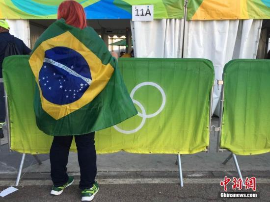 当地时间8月5日,2016里约奥运会开幕式将在里约热内卢的马拉卡纳体育场举行。图为身披巴西国旗的观众。<a target='_blank' href='http://www.chinanews.com/' >中新网</a>记者 张素 摄