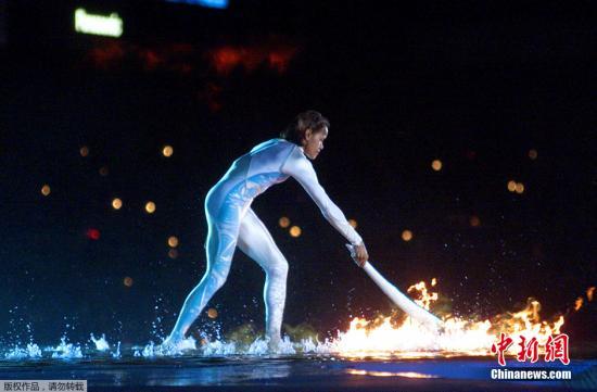 """悉尼还把水与火完美地结合在一起,在瀑布中央点燃圣火极大地刺激了人类的想像力,奥运会开幕式也因此成为了各主办国竞逐各自创意的舞台。开幕式上点燃圣火的运动员,身穿银色连体防水服,在瀑布背景下点燃火炬,上演了一幕""""水中燃火""""的精彩大戏。"""