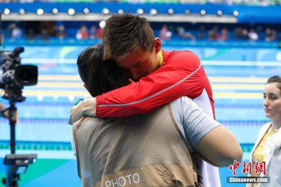 北京时间8月7日,在里约奥运会游泳男子400米自由泳比赛中,中国选手孙杨遗憾摘银,澳大利亚选手霍顿摘得金牌。图为赛后一位摄影记者拥抱安慰孙杨。记者 富田 摄